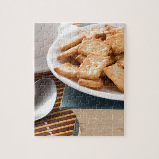 White plate with cookies on the old book jigsaw puzzle