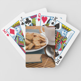 White plate with cookies on the old book poker deck