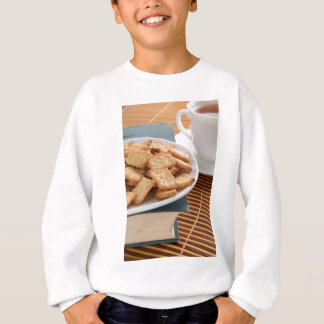 White plate with cookies on the old book sweatshirt