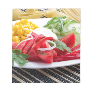White plate with slices of fresh tomatoes notepad
