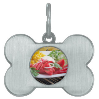 White plate with slices of fresh tomatoes pet ID tag