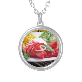 White plate with slices of fresh tomatoes silver plated necklace