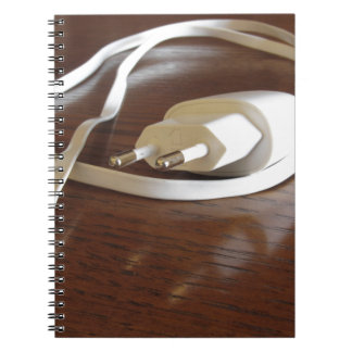 White smartphone charger on wooden table spiral notebook