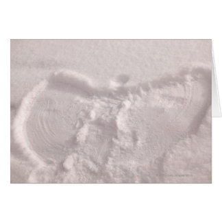 White snow imprinted with a snow angel card