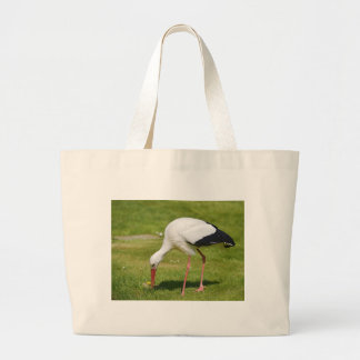 White stork on grass large tote bag