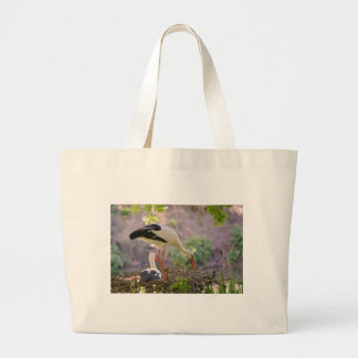 White storks on its nest large tote bag