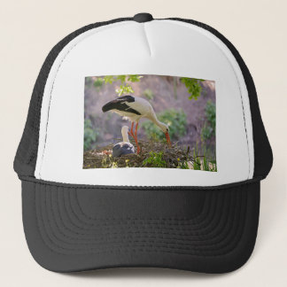 White storks on its nest trucker hat