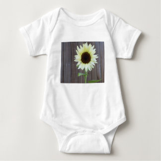 White sunflower against a weathered fence baby bodysuit