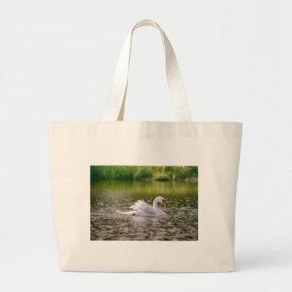 White swan on a lake large tote bag