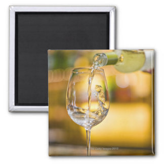White wine is poured from bottle in restaurant. refrigerator magnet