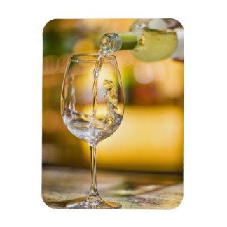 White wine is poured from bottle in restaurant. rectangular photo magnet