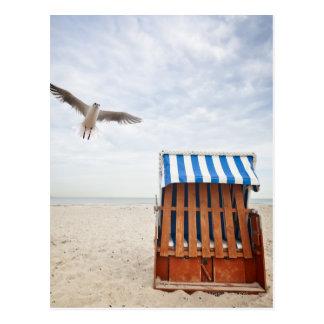 Wicker beach chair on beach postcard