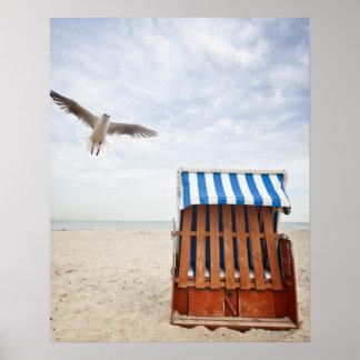 Wicker beach chair on beach poster