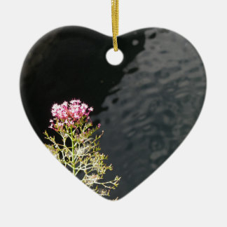 Wildflowers against the water surface of a river ceramic heart decoration