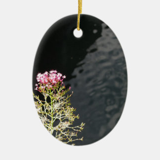 Wildflowers against the water surface of a river ceramic oval decoration