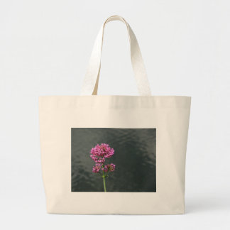 Wildflowers against the water surface of a river large tote bag