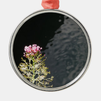 Wildflowers against the water surface of a river Silver-Colored round decoration