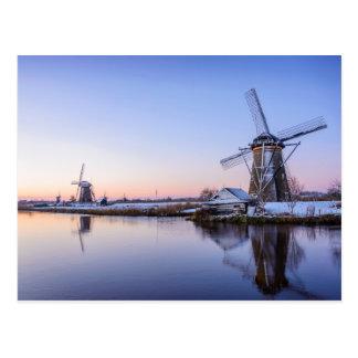 Windmills in winter along a frozen river postcard