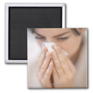 Woman blowing her nose. square magnet