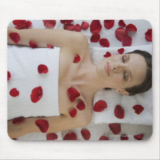 Woman covered in flower petals laying on massage mouse pad
