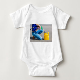 Woman filling yellow can with gasoline or petrol. baby bodysuit