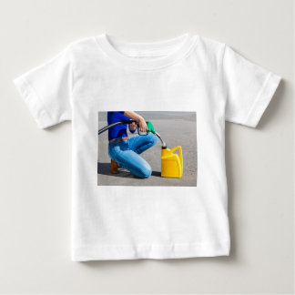 Woman filling yellow can with gasoline or petrol. baby T-Shirt