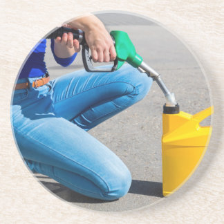 Woman filling yellow can with gasoline or petrol. coaster