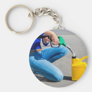 Woman filling yellow can with gasoline or petrol. key ring