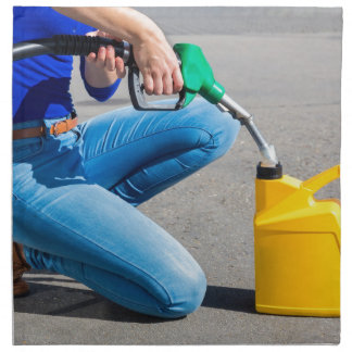Woman filling yellow can with gasoline or petrol. napkin