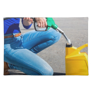 Woman filling yellow can with gasoline or petrol. placemat