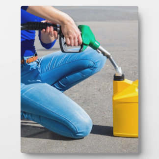 Woman filling yellow can with gasoline or petrol. plaque