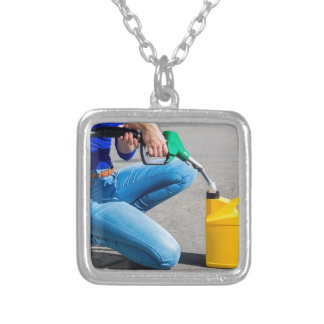 Woman filling yellow can with gasoline or petrol. silver plated necklace