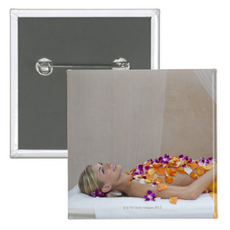 Woman getting a flower treatment at a spa. 15 cm square badge