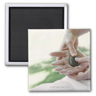 Woman getting hand massage with hot stone square magnet