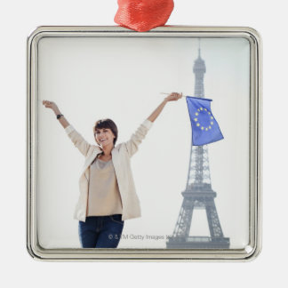 Woman holding a European Union flag and a French Christmas Tree Ornaments