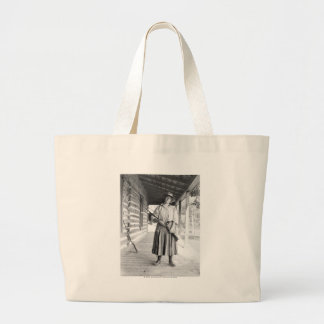Woman holding a rifle on a porch tote bag