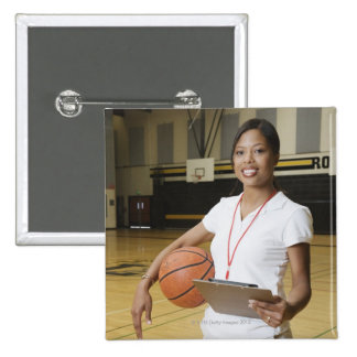 Woman holding basketball and clipbpard, smiling, pinback buttons