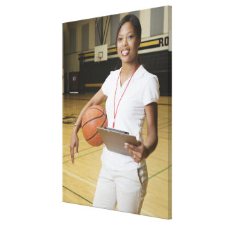 Woman holding basketball and clipbpard, smiling, stretched canvas prints