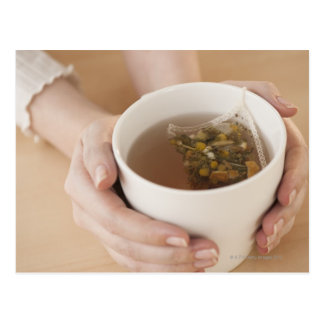 Woman holding cup with chamomile tea postcard