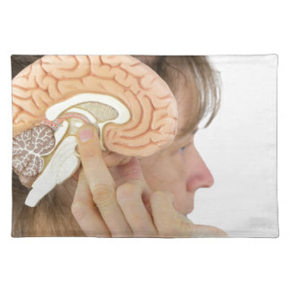 Woman holding hemisphere model  against head placemat