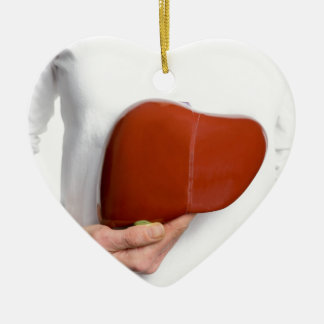 Woman holding human liver model at white body ceramic ornament