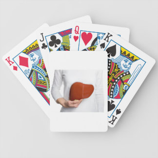Woman holding human liver model at white body poker deck