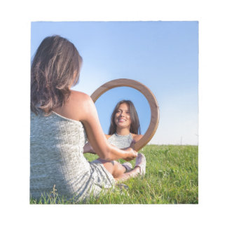 Woman in nature viewing her mirror image notepad