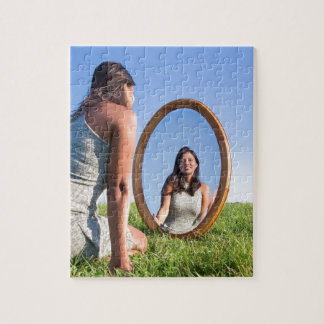 Woman kneeling on grass looking at mirror image puzzles