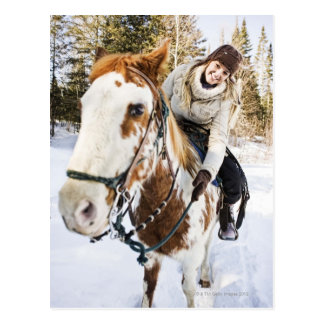 Woman on horse outdoors during winter postcard
