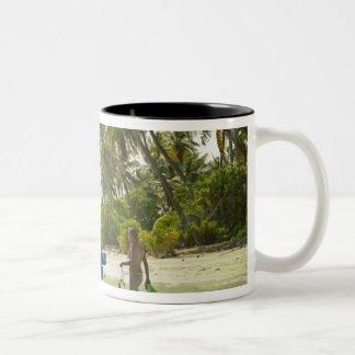 Woman on small traditional fishing boat, mugs
