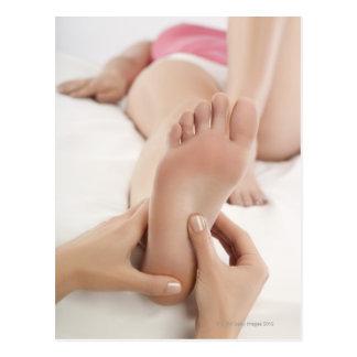 Woman receiving foot massage postcard