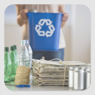 Woman recycling plastic bottles, cans and sticker