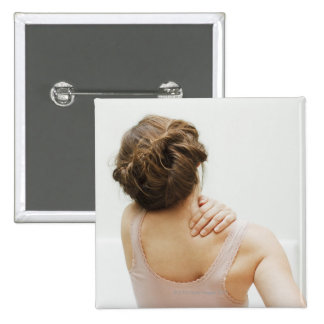Woman rubbing aching back 15 cm square badge