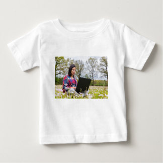 Woman sits with laptop in blooming meadow baby T-Shirt